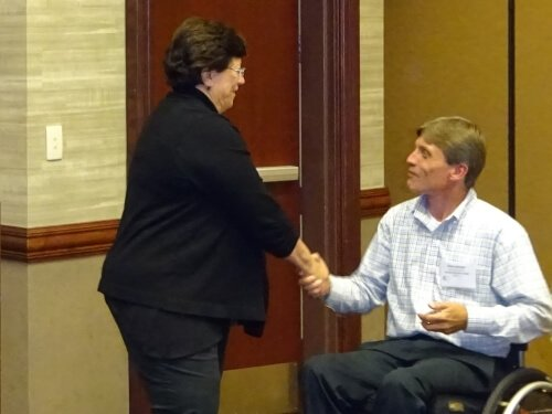 Lynne Clark, chief of the National Information Assurance Education and Training Program (NIETP), congratulates Professor Steve Carrigan of Danville Community College